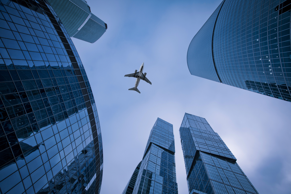 Photo of an airplane above the glass office buildings