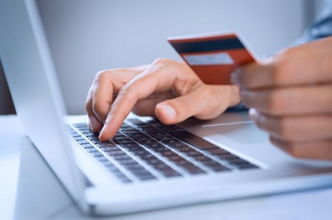 Zdjęcie Close Up Of A Man Shopping Online Using Laptop With Credit Card pochodzi z serwisu ShutterStock