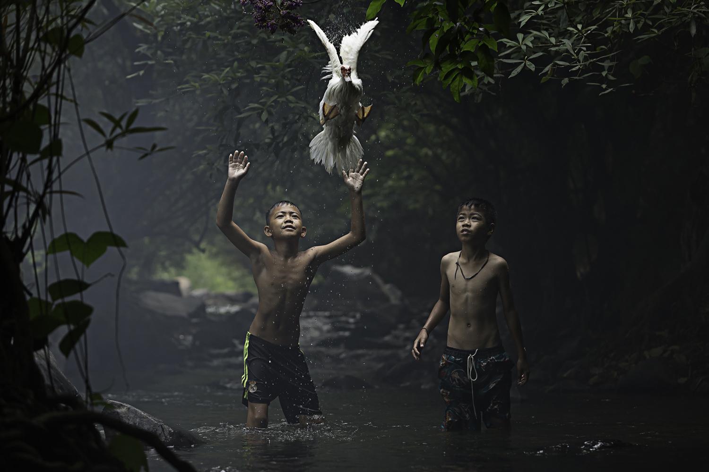 Autor: Sarah Wouters. Chłopcy łapiący kaczkę w pobliżu wodospadu. Wyróżnienie